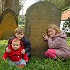 Thumbnail photo of my children with the grave of their six-greats grandparents
